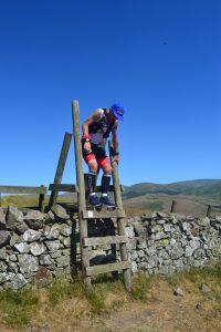 climbing over stile on Saint Cuthbert's Way Ultra
